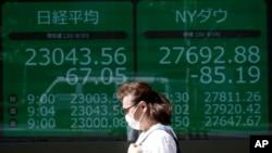 ស្ត្រីម្នាក់ដើរកាត់ពីមុខតារាងផ្សារហ៊ុន Nikkei និងផ្សារហ៊ុន Dow របស់ញូវយ៉ក នៅក្នុងទីក្រុងតូក្យូកាលពីថ្ងៃទី២០ ខែសីហា ឆ្នាំ២០២០។