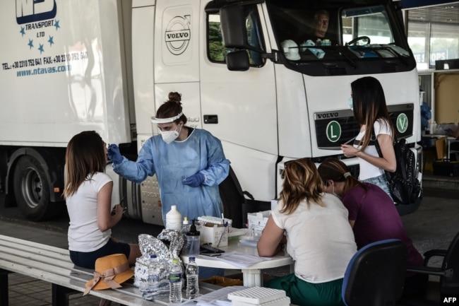 Seorang petugas kesehatan mengumpulkan sampel swab untuk menguji Covid-19, di Promachonas, perbatasan Yunani-Bulgaria, 10 Juli 2020. (Foto: dok).