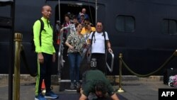 A passenger reacts as he disembarks from the Westerdam cruise ship in Sihanoukville, Cambodia, where the liner docked after being refused entry at other Asian ports due to fears of the COVID-19 coronavirus outbreak.