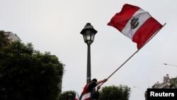 Un partisan du candidat présidentiel péruvien Pedro Castillo brandit le drapeau national au lendemain du second tour des élections, à Lima, au Pérou, le 7 juin 2021.