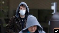 一個戴著口罩的男子從華盛頓州柯克蘭市生命護理中心的入口離開(2020年3月3日)。