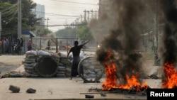 曼德勒街頭的一位反政變示威者在一處路障附近做出手勢。 (2021年3月22日)