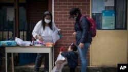 La residente colombiana Alba Rada regala artículos de tocador y comida a la migrante venezolana Rosmira Camacho y su hijo, afuera de la casa de Rada donde dirige su fundación, Radaber, en Tocancipá, Colombia, el martes 6 de octubre de 2020.