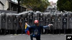 وینزویلا میں حزبِ اختلاف کا ایک حامی پولیس اہلکاروں کے سامنے احتجاج کر رہا ہے۔ (فائل فوٹو(