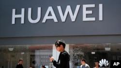 Para pejalan kaki berjalan melewati toko retail Huawei di Beijing, 30 Juni 2019. (AP Photo)