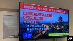 지난 21일 미국 시애틀 공항에 설치된 모니터 화면에 우한 폐렴 의심 증상 발생 시 대처 요령에 관한 중국어 안내문이 나오고 있다.