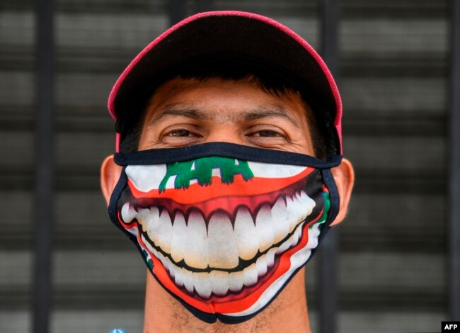 A street vendor wearing a face mask poses outside the central market in San Salvador on May 6, 2020, amid the COVID-19 coronavirus pandemic. (Photo by Yuri CORTEZ / AFP)