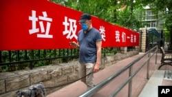 Một người đàn ông đeo khẩu trang đi ngang biểu ngữ tuyên truyền kêu gọi người dân phân loại rác ở Bắc Kinh, Trung Quốc, ngày 24 tháng 6, 2020.
