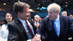 Jeremy Hunt, left, congratulates Boris Johnson after the announcement of the result in the ballot for the new Conservative party leader, in London, Tuesday, July 23, 2019.