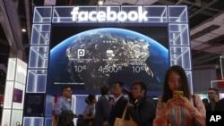 ພວກຜູ້ທ່ຽວຊົມ ຍ່າງຜ່ານຮ້ານສື່ສັງຄົມຍັກໃຫຍ່ ເຟສບຸກ Facebook ຢູ່ທີ່ງານວາງສະແດງສິນຄ້າ ສົ່ງອອກ-ນຳເຂົ້າສາກົນ ນະຄອນຊຽງໄຮ້, ວັນທີ 6 ພະຈິກ 2019.