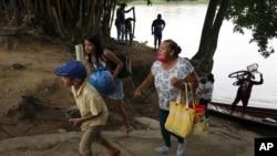 Una familia venezolana lleva sus pertenencias luego de cruzar el río Arauca en bote para salir de Venezuela, en Arauquita, Colombia, el jueves 25 de marzo de 2021.