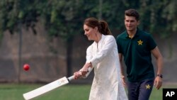 Britain's Kate, Duchess of Cambridge, bats as Pakistani cricketer Shaheen Afridi looks on during her visit to the Pakistan Cricket Academy in Lahore, Pakistan, Oct. 17, 2019.