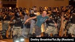 Para petugas penegak keamanan mengawal seorang pria saat bentrokan dengan para pendukung oposisi setelah pemungutan suara ditutup, di Minsk, Belarusia, 9 Agustus 2020.
