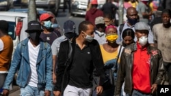 People wearing face masks to protect against coronavirus, walk on the street in downtown Johannesburg, South Africa, May 11, 2020.
