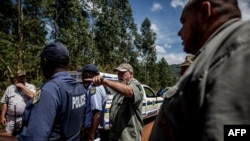 FILE - A white farmer (C) speaks to police after an incident in which a worker was held at gunpoint, in Tzaneen, South Africa, Nov. 2, 2017.