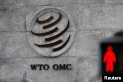 FILE - A logo is pictured outside the World Trade Organization (WTO) headquarters next to a stop sign, in Geneva, Switzerland.