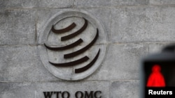 A logo is pictured outside the World Trade Organization (WTO) headquarters next to a stop sign, in Geneva, Switzerland.