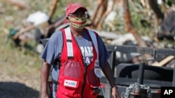 FILE - A Red Cross volunteer wears a face mask while visiting tornado-damaged residences in Prentiss, Miss., April 14, 2020. Additional storms on April 19, 2020, were blamed for three deaths.