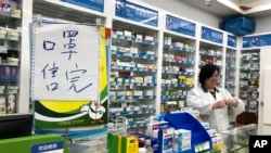 "Pharmacist Liu Zhuzhen stands near a sign reading ""face masks are sold out"" at her pharmacy in Shanghai, China, Jan. 21, 2020."