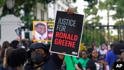 FILE - Demonstrators stand in front of the governor's mansion after a march from the state Capitol in Baton Rouge, La., May 27, 2021, protesting the death of Ronald Greene, who died in the custody of Louisiana State Police in 2019.
