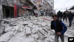 Warga berjalan di antara puing-puing bangungan menyusul serangan udara oleh pasukan pemerintah, di Ariha, Provinsi Idlib, Suriah, 15 Januari 2020.