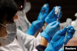 FILE - Health care workers prepare doses of the Moderna coronavirus vaccine before administering them to staffers of Japan's supermarket group Aeon at the company's shopping mall in Chiba, Japan, June 21, 2021.