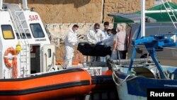 Petugas layanan darurat membawa jenazah korban kapal migran yang terbakar di lepas pantai Crotone, ke dermaga Le Castella , Italia, 30 Agustus 2020.