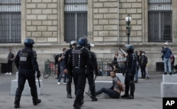 Police detain a protester during a demonstration in Paris, France, July 31, 2021. Demonstrators gathered in several cities to protest against the COVID-19 pass, which grants vaccinated individuals greater ease of access to venues.