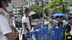 Orang-orang antre untuk mengisi tabung oksigen medis di tempat pengisian ulang di Pazundaung, Yangon, Myanmar, Minggu, 11 Juli 2021.