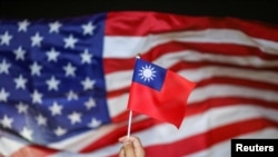 FILE - An anti-government protester holds a Taiwan national flag as a US flag flutters in the background during a demonstration to celebrate Taiwan's National Day in Hong Kong, China Oct. 10, 2019.