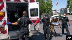 Salem Fire Department paramedics and employees of Falck Northwest ambulances respond to a heat exposure call during a heat wave, June 26, 2021, in Salem, Ore.