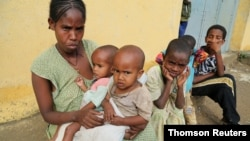 FILE - A displaced single mother is seen with her five children in Nebelet, Tigray region, Ethiopia, July 11, 2021.