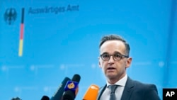 FILE - German Foreign Minister Heiko Maas briefs the media during a news conference on current developments in the worldwide spread of the coronavirus at the foreign ministry in Berlin, Germany, Tuesday, March 17, 2020.