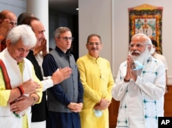 This photograph provided by the Prime Minister's Office shows Indian Prime Minister Narendra Modi, right, greeting members of various political parties before the start of their meeting in New Delhi, June 24, 2021.
