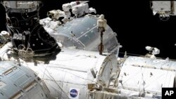 En esta imagen captada de un vídeo, los astronautas de la NASA Mike Hopkins, centro derecha, y Victor Glover, centro izquierda, trabajan en el laboratorio europeo de la Estación Espacial Internacional, el 27 de enero pasado.