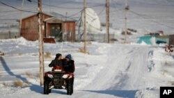 Residentes de Toksook Bay, Alaska, se movilizan en vehículos para todo terreno.