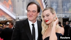 Margot Robbie and Quentin Tarantino pose on the red carpet during the Oscars arrivals at the 92nd Academy Awards in Hollywood, Feb. 9, 2020.