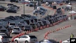 Múltiples automóviles hacen fila para ingresar a un centro de vacunación contra el COVID-19 en el Dodger Stadium, en Los Ángeles, el 25 de febrero de 2021.