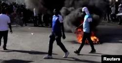 Un neumáticos en llamas el domingo 28 de febrero de 2021 en nuevas portestas en Haití. [Captura de pantalla/Video de Reuters]