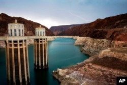 FILE - In this July 28, 2014, photo, lightning strikes over Lake Mead near Hoover Dam that impounds Colorado River water at the Lake Mead National Recreation Area in Arizona.