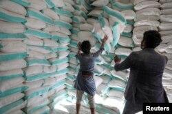 Workers handle sacks of wheat flour at a World Food Program food aid distribution center in Sanaa, Yemen, Feb. 11, 2020.