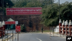A soldier stands guard at a checkpoint next to a military propaganda billboard in Mandalay, Myanmar, Feb. 3, 2021.