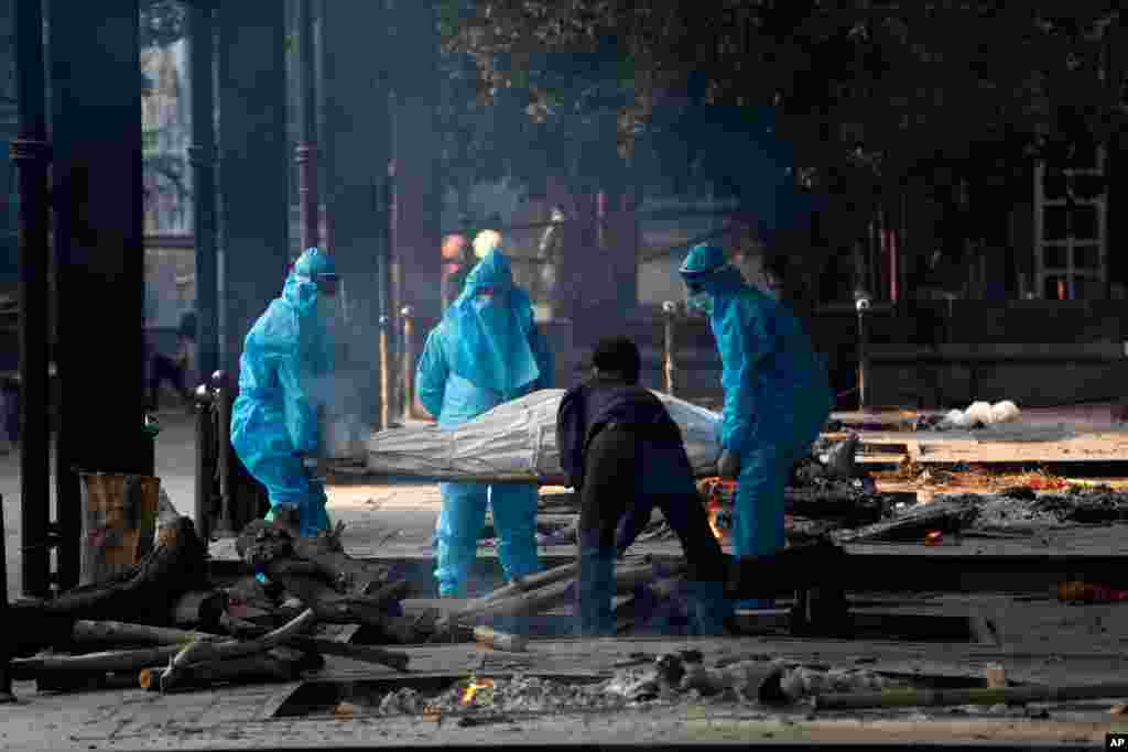 Health workers in personal protective equipment carry the body of a COVID-19 victim for cremation in New Delhi, India,.