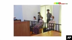 FILE - A screen grab from Myawaddy TV video shows deposed Myanmar leader Aung San Suu Kyi (center-left) and President Win Myint (center) appear before a special court in Naypyitaw, May 24, 2021.