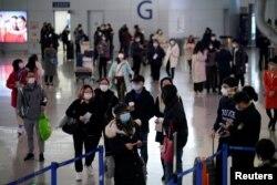 Passengers wearing masks are seen at Pudong International Airport, in Shanghai, China, Jan. 27, 2020.