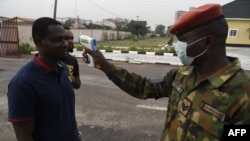 A soldier checks the body temperature of a visitor to the 68 Nigerian Army Reference Hospital at Yaba in Lagos, on February 28, 2020. - Nigeria reported the first new coronavirus case in sub-Saharan Africa on February 28, 2020 and a major global…