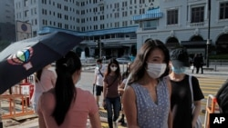 People wearing masks to protect against the coronavirus, walk across a street in Hong Kong, Aug. 20, 2020.
