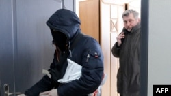 Chief of Belarusian Association of Journalists (BAJ) Andrei Bastunets, right, and Belarusian policemen leaves the BAJ office after raid in Minsk, on Feb. 16, 2021.