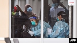 Medical staff perform a coronavirus test on a resident of public housing unit during a spike in infections, in Melbourne, Australia, July 6, 2020.