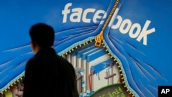 FILE - A man walks past a mural in an office on the Facebook campus in Menlo Park, Calif., June 11, 2014.